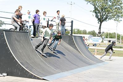 Kiwanis Park - Several youth skateboarding down ramp